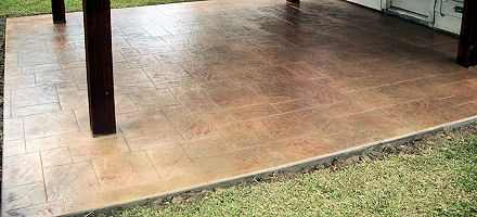 New concrete patio with tile design, in backyard of a small home